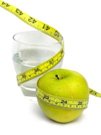 Glass of Water and Green Apple with measuring tape