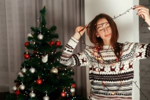 Brunette woman in white reindeer sweater holdi