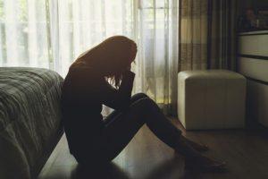 depressed woman sitting in the dark bedroom