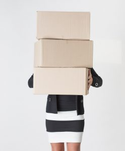 Young adult female carry a stack of boxes during a move from one office to another